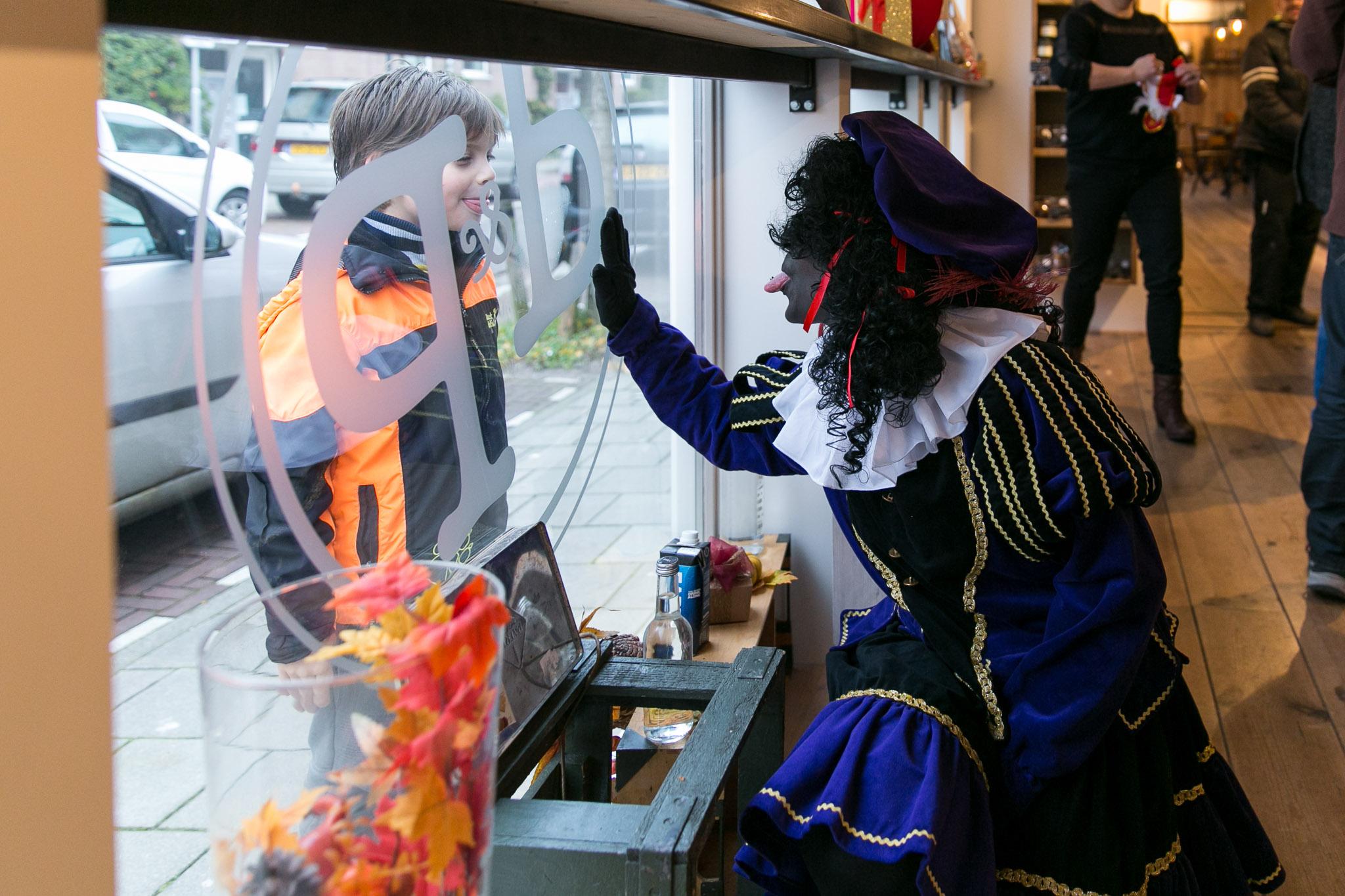 Ontmoeting met zwarte piet en jongetje bij de bakker tijdens een Day in the life fotoshoot