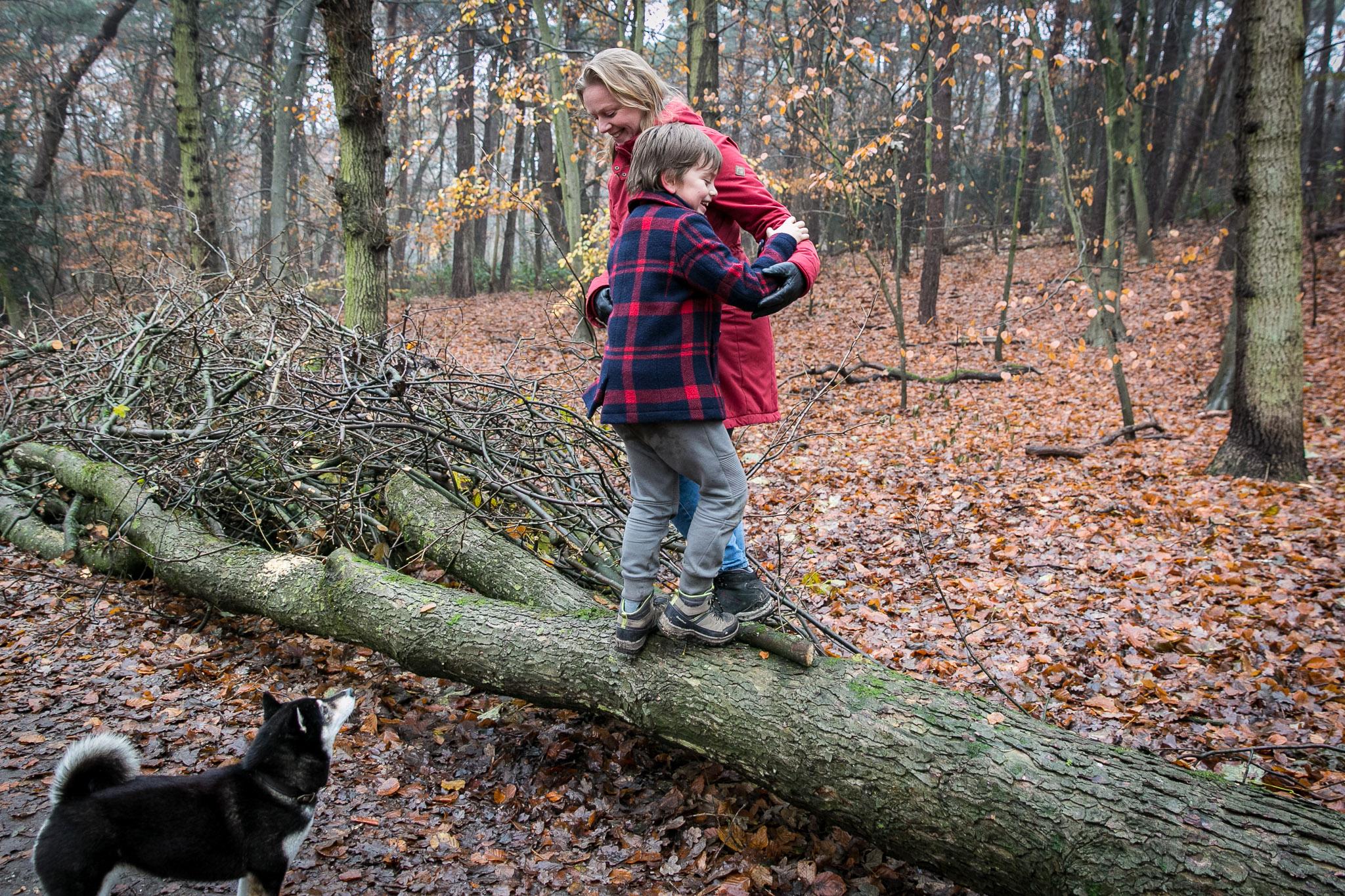 Moeder en zoon dollen in het bos tijdens fotoshoot