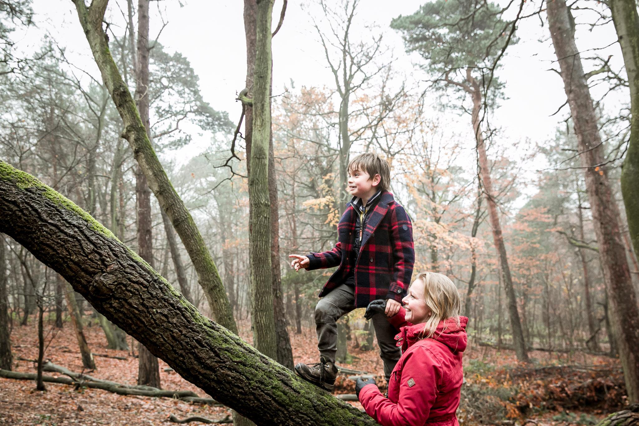 Moeder helpt zoon als hij op een boomstam klimt