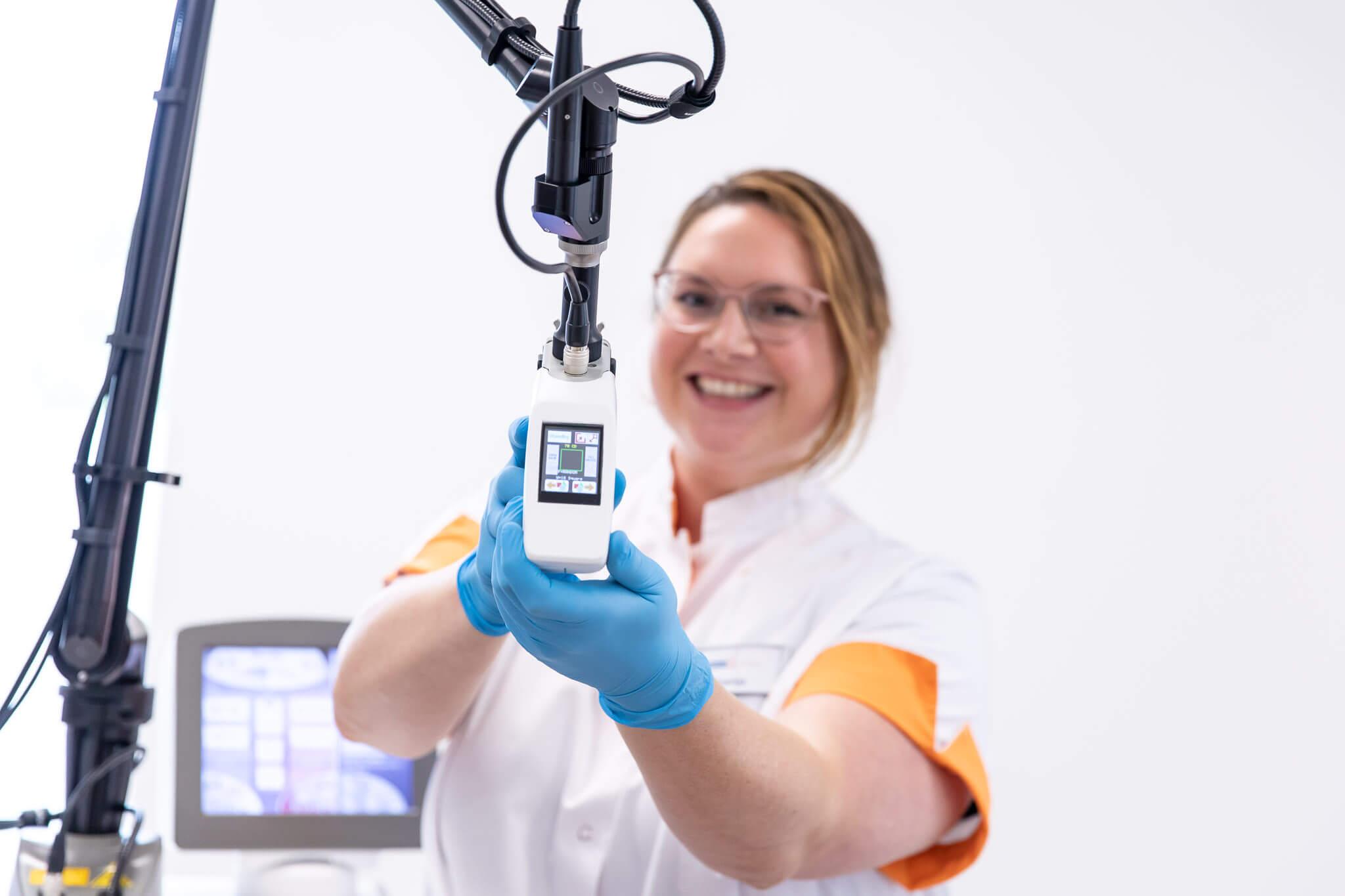 Een medewerker van Mediderma laat het nieuwe laserapparaat zien bij Mediderma in Purmerend