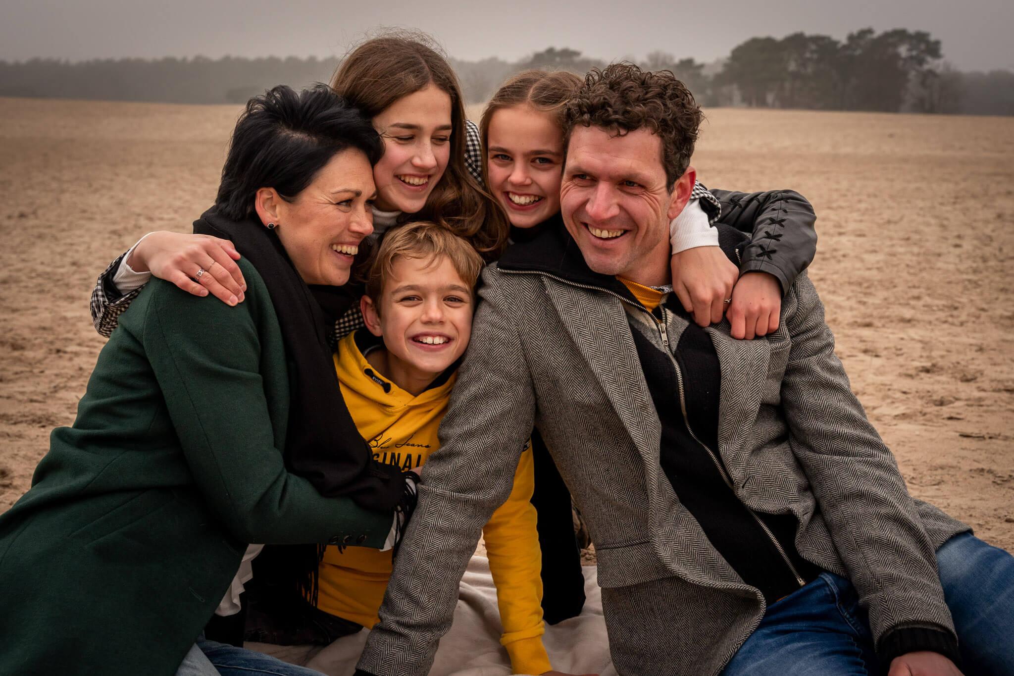 De familie op de foto op een koude winterdag in de Soesterduinen