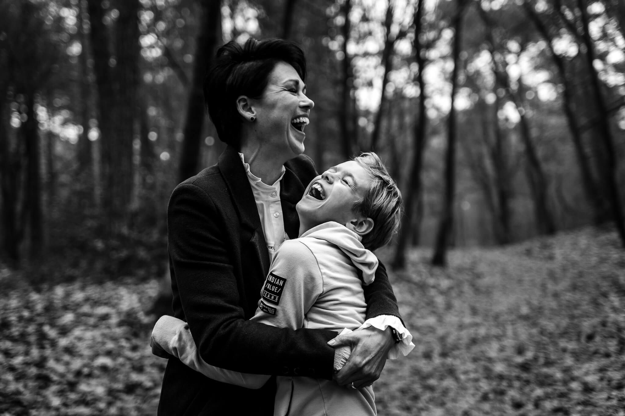 Moeder en zoon moeten heel hard lachen tijdens de familieshoot